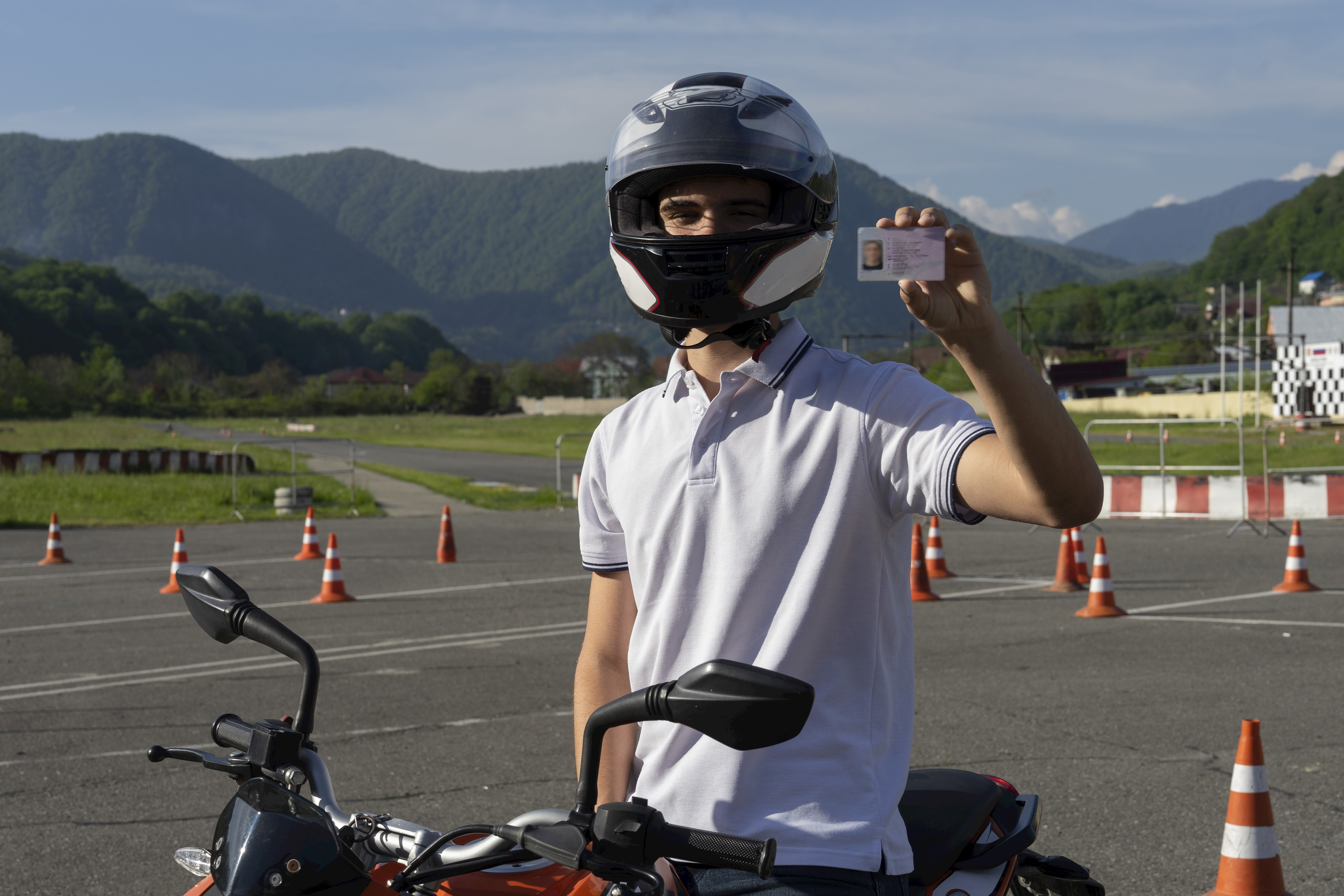 Young man in a helmet on the motorbike is showing driving license © Aleksandr - AdobeStock_266570822.jpeg
